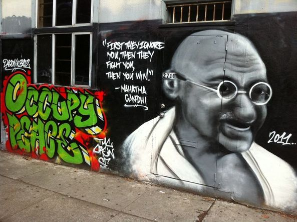 A wall graffiti in San Francisco containing a quote and image of Gandhi