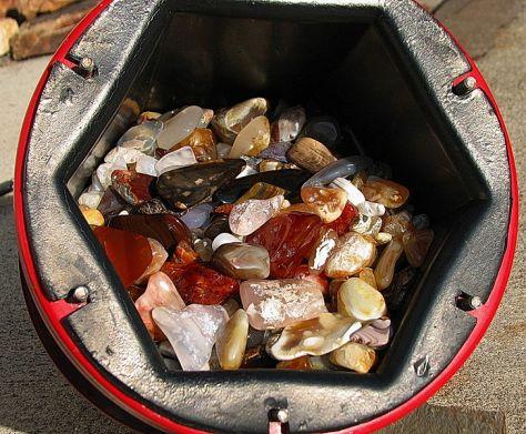 A 15 pound (6.8 kg) tumbler barrel full of glistening tumble-polished agate and jasper.
