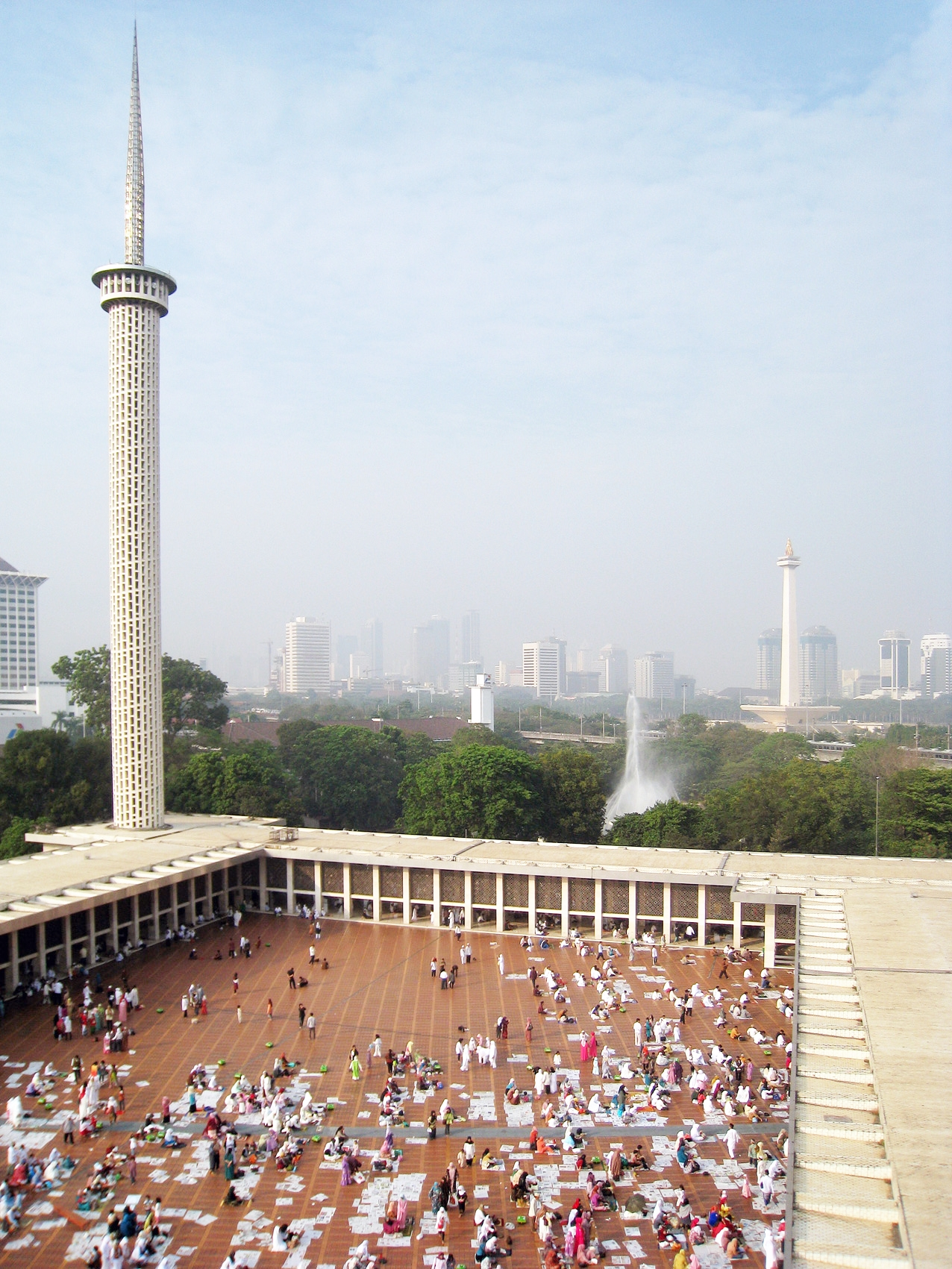 The minaret or tower of Istiqlal Mosque, Jakarta, Indonesia. The National Monument (Monas) and Medan Merdeka Square in the background with Jakarta skyline.