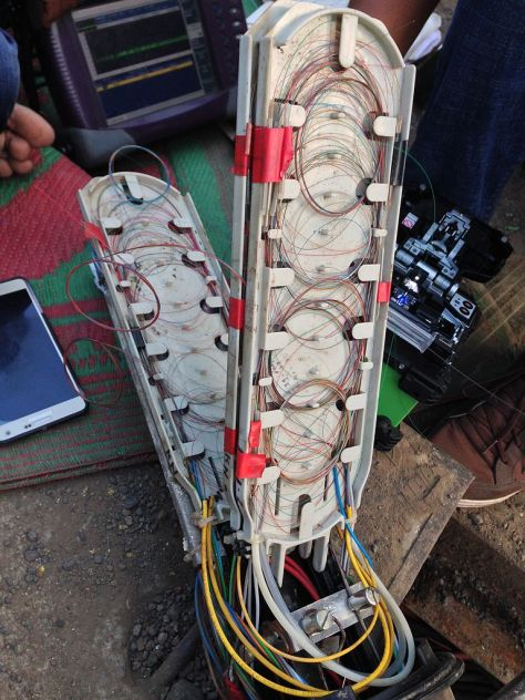 Technicians_investigating_a_fault_in_an_optical_fiber_cable_junction_box